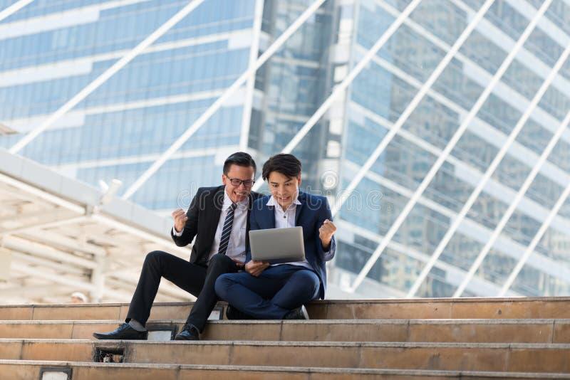 愉快亚洲人两的商人,当选址看见膝上型计算机时 在busi 免版税库存照片
