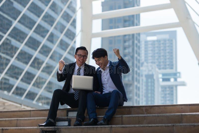 愉快亚洲人两的商人,当选址看见膝上型计算机时 在busi 库存图片