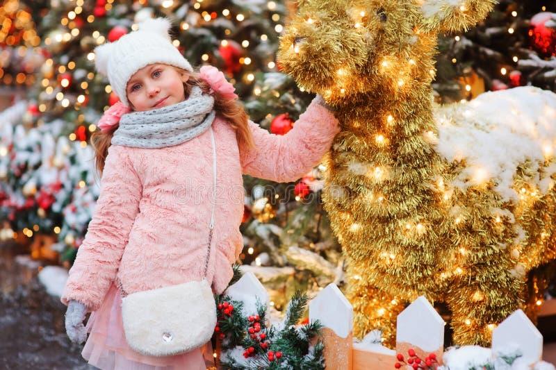 愉快儿童女孩使用室外在步行在新年假日装饰的多雪的冬天城市 免版税库存图片