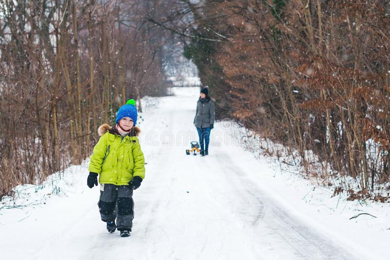 愉快冬天步行的小男孩 有获得的母亲的愉快的孩子乐趣户外 一起享受消费的时间 美丽多雪 库存图片