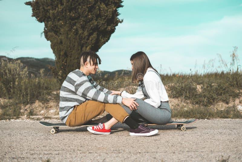 愉快千福年的年轻的夫妇获得与溜冰板运动的乐趣 实践滑冰的年轻人 库存照片