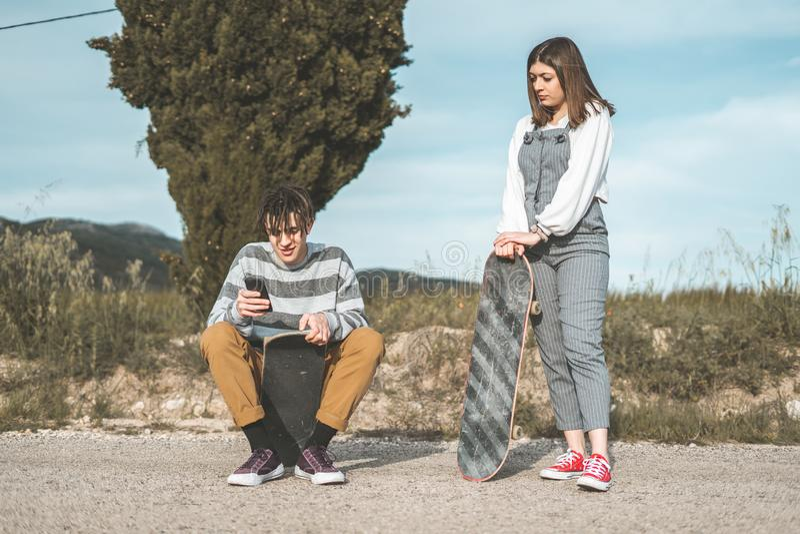 愉快千福年的年轻的夫妇获得与溜冰板运动的乐趣 实践滑冰的年轻人 免版税库存图片