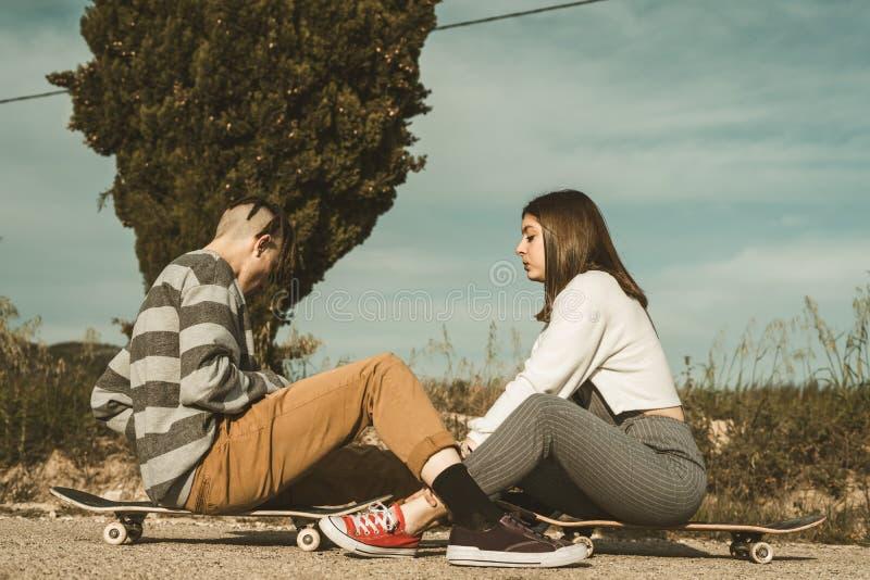 愉快千福年的年轻的夫妇获得与溜冰板运动的乐趣 实践滑冰的年轻人 免版税库存照片