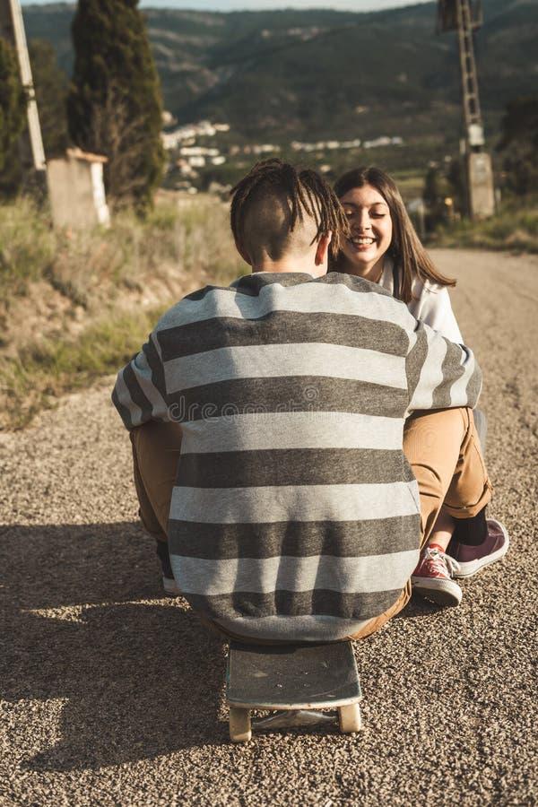 愉快千福年的年轻的夫妇获得与溜冰板运动的乐趣 实践滑冰的年轻人 图库摄影