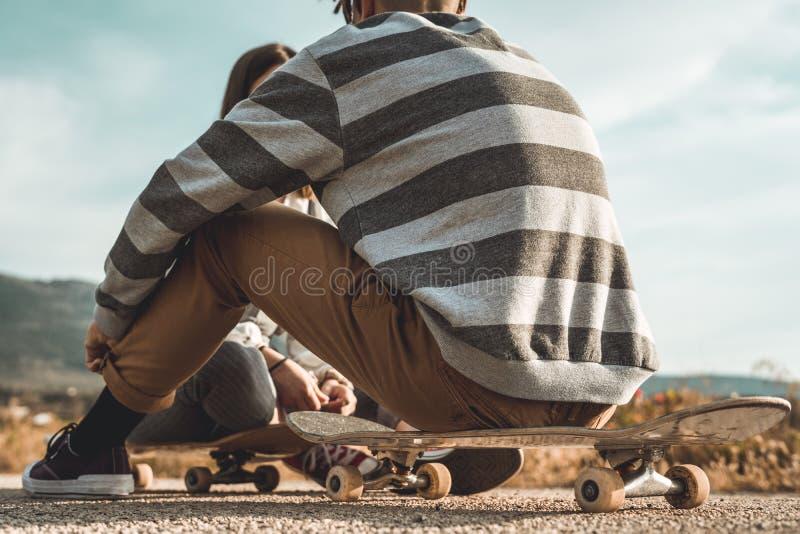 愉快千福年的年轻的夫妇获得与溜冰板运动的乐趣 实践滑冰的年轻人 库存图片