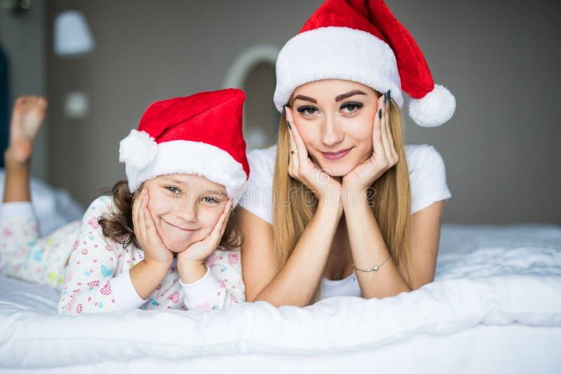愉快卧室的系列 户内母亲和孩子在圣诞老人帽子在床上 获得的人们乐趣在家 圣诞节Xmas新年wint 免版税库存图片