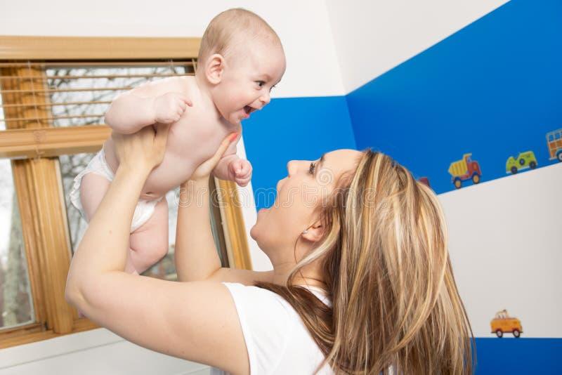 愉快可爱的婴孩她亲吻的母亲照片 免版税图库摄影