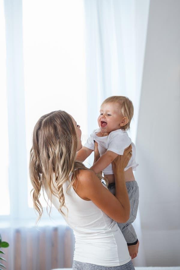 愉快可爱的婴孩她亲吻的母亲照片 免版税库存图片