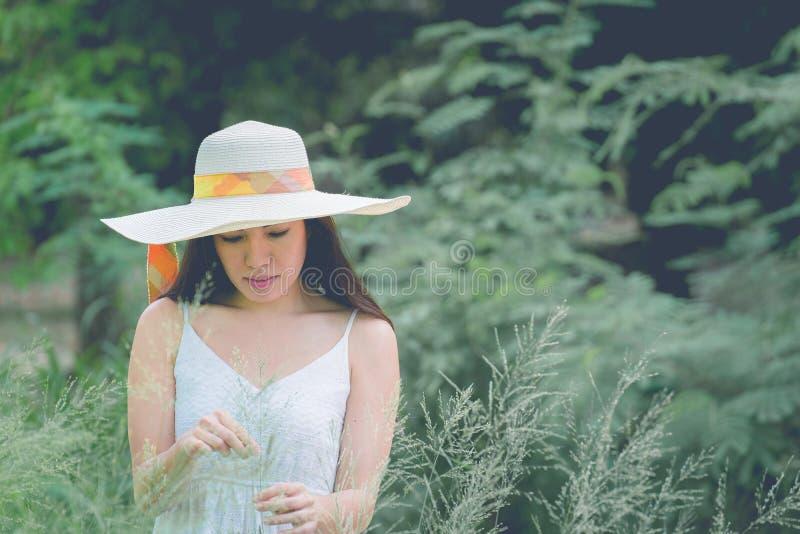 愉快和享用的少妇画象一个草甸的在一个晴朗的夏日 免版税库存图片