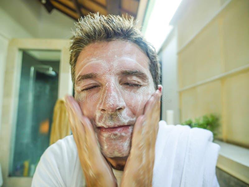 愉快和可爱的白种人洗他的与exfoliant肥皂的人微笑的新鲜的在家卫生间面孔看他自己在toile 免版税库存照片