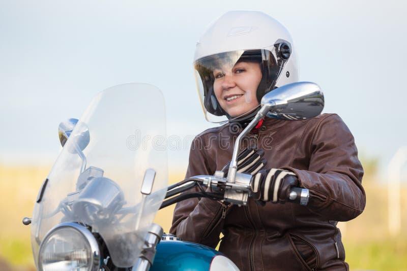 愉快和微笑的妇女摩托车骑士准备好对在皮夹克和白色安全帽的操纵的砍刀,户外 库存图片