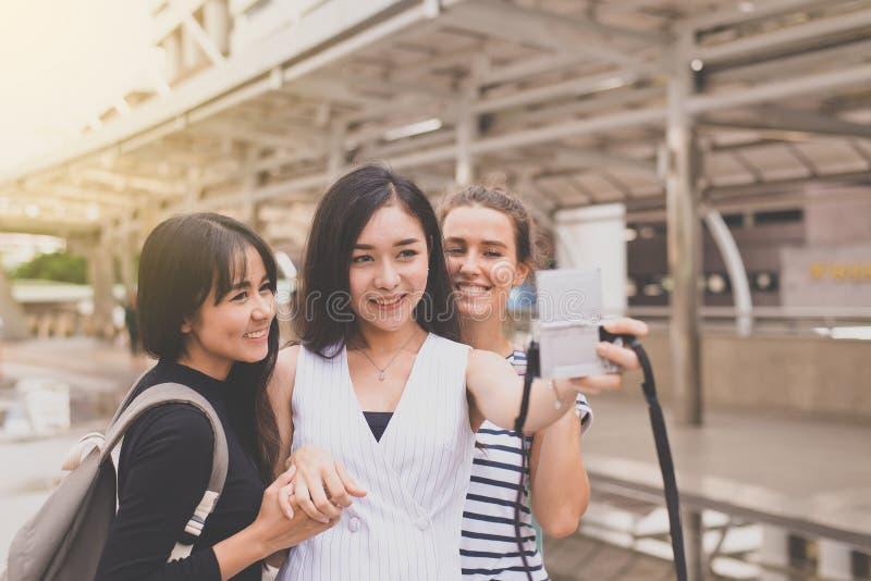 愉快和微笑的小组妇女旅客在城市做她的与数码相机,走在的美女朋友的selfie 免版税库存照片