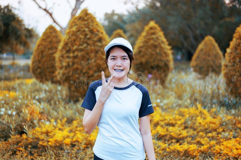 愉快和微笑的年轻亚洲妇女身分和rais手,当休假时在跑在公园以后,正面认为 免版税库存图片