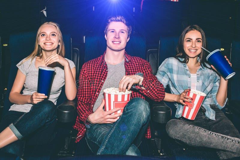 愉快和快乐的人民是坐和观看电影 他们是激动的 白肤金发的女孩食用一个杯子可乐 人举行a 库存图片