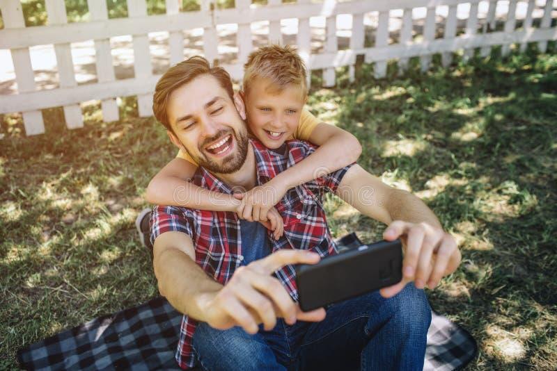 愉快和快乐的家庭一起坐并且采取selfie 男孩拥抱他的爸爸 人举行电话和微笑 库存图片