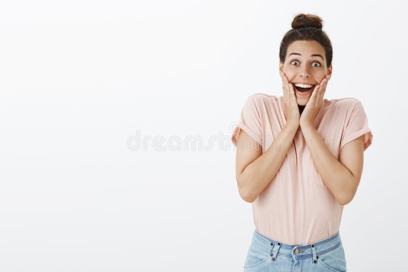 愉快和快乐的惊奇的年轻可爱的女孩用在握在面颊微笑的桃红色时髦的T恤杉的杂乱小圆面包手 免版税库存照片