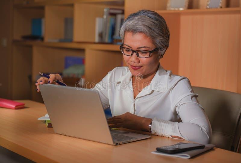 愉快和成功的有吸引力的中部公司工作生活方式画象变老了工作在办公室手提电脑书桌的亚裔妇女 免版税库存图片
