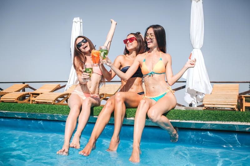 愉快和正面少妇坐在游泳池边缘  他们舒展他们的身体和欢呼 妇女是激动的 免版税库存图片