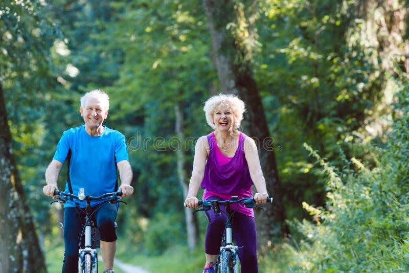 愉快和活跃资深夫妇骑马在公园骑自行车户外 免版税库存图片