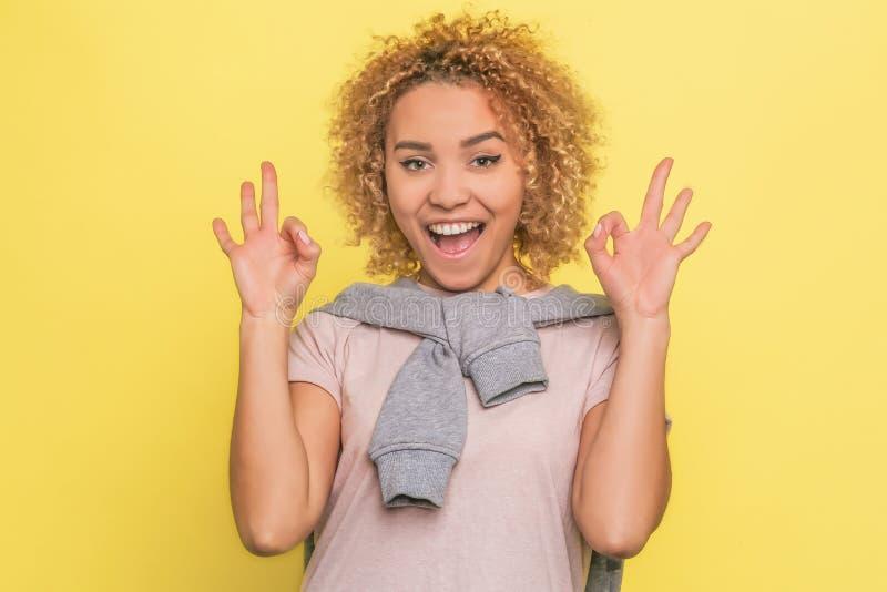 愉快和满意的女孩是站立和显示与她的手指的好标志 她看对照相机 查出 库存图片