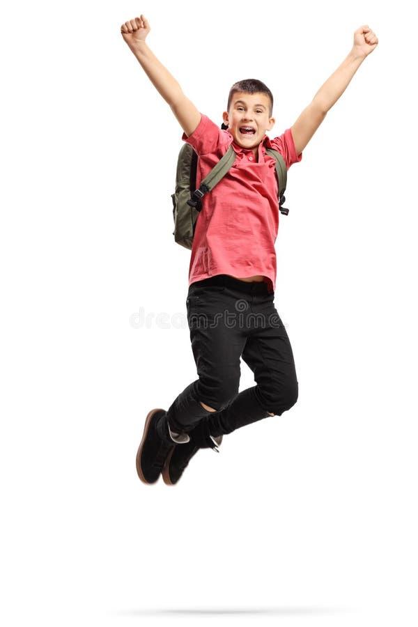 愉快和激动少年男小学生跳跃 免版税图库摄影