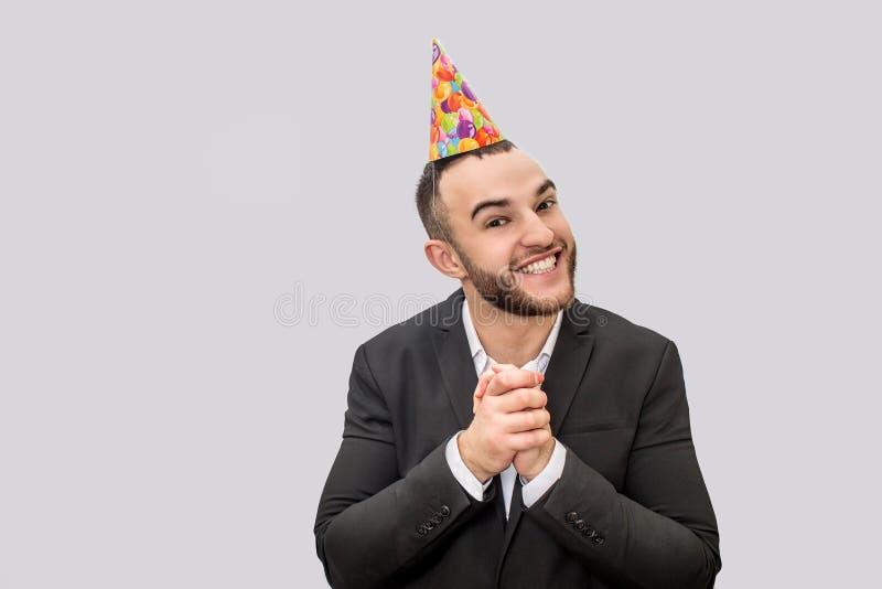 愉快和激动的年轻人一起保留手 他在照相机和微笑看 人佩带在头的欢乐锥体 查出 免版税库存照片