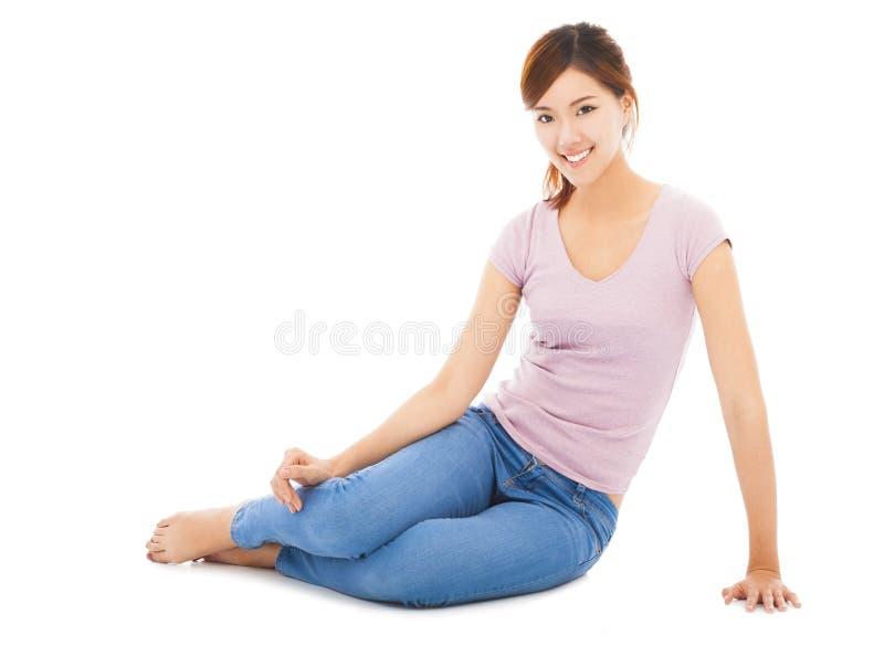 愉快和美丽的年轻学生坐地板 免版税库存照片