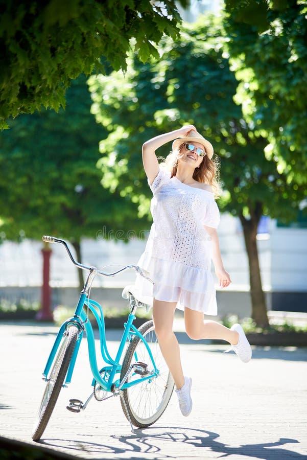 愉快和跳跃在蓝色自行车旁边的白色礼服的正面年轻女性在市中心 免版税库存照片