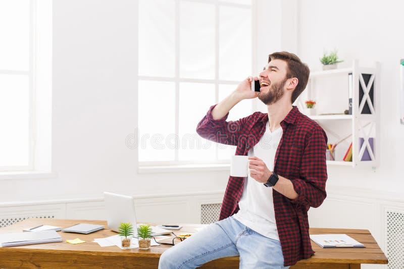 愉快和轻松的商人谈话机动性在办公室 免版税库存图片