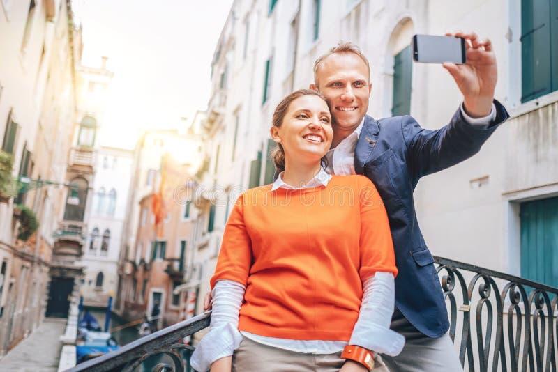 愉快在爱夫妇在威尼斯,意大利拍在一个的selfie照片许多桥梁 旅行 免版税库存照片