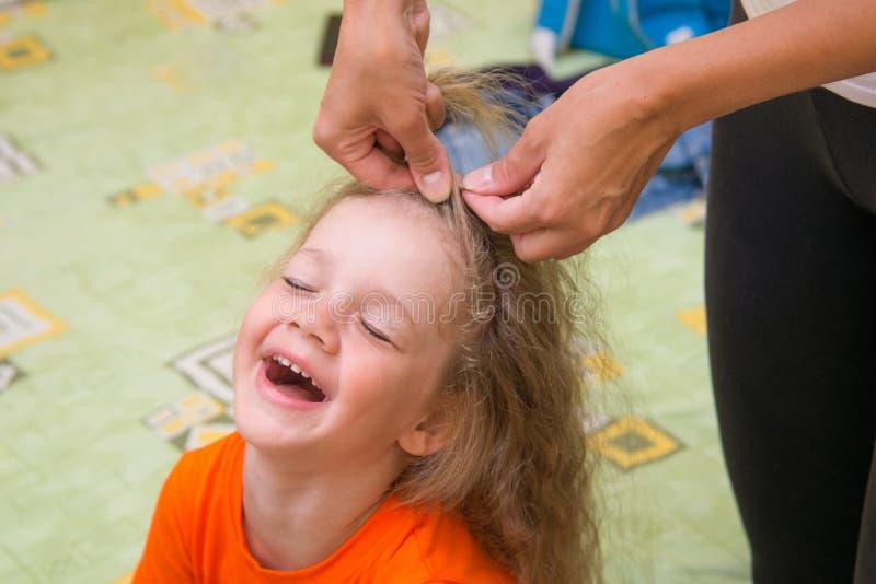 愉快地坐四的岁的女孩,当她做她的头发 图库摄影