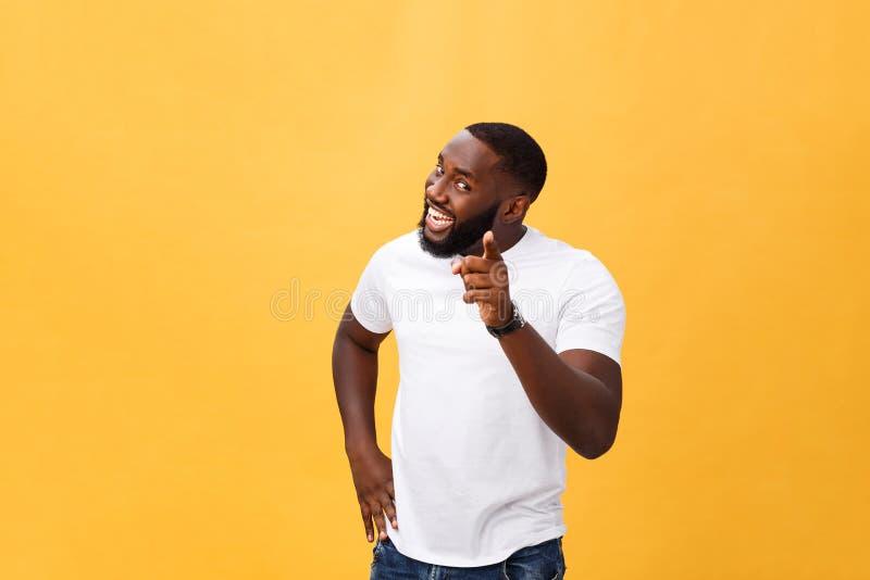 愉快地微笑和把他的食指指向的滑稽的年轻非洲顾客照相机,好象选择您和邀请 免版税库存图片