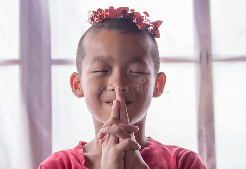愉快地微笑和站立在演播室的逗人喜爱的亚裔小男孩 库存图片
