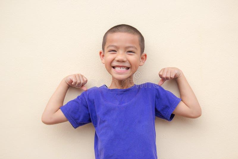 愉快地微笑和站立在演播室的逗人喜爱的亚裔小男孩 免版税图库摄影