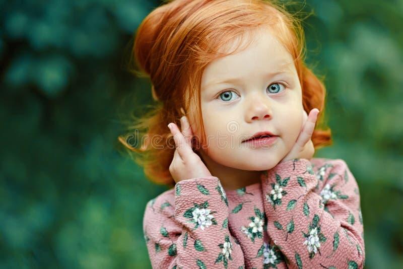 愉快地微笑,在summ的小美丽的红发小女孩 库存照片