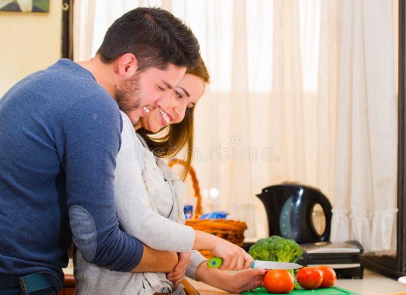 愉快地拥抱有吸引力的年轻的夫妇,当一起砍菜,烹调与爱概念时 免版税库存图片