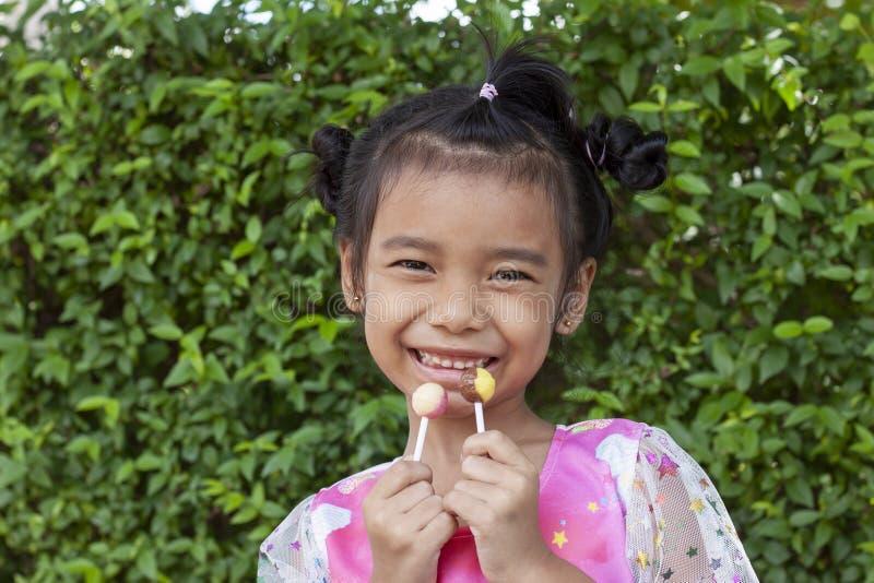 愉快地拿着棒棒糖的女孩的两只手 免版税图库摄影