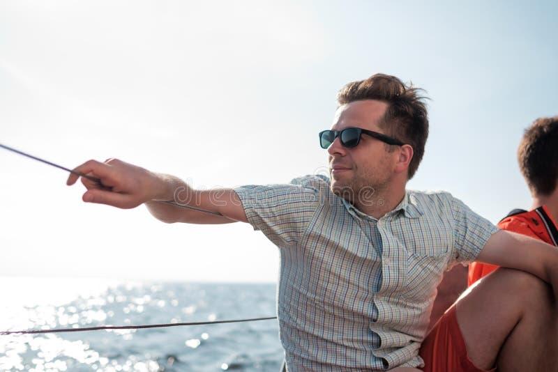 愉快地放松在风船游艇的年轻白种人水手 他在旁边loooks和梦想 免版税库存图片