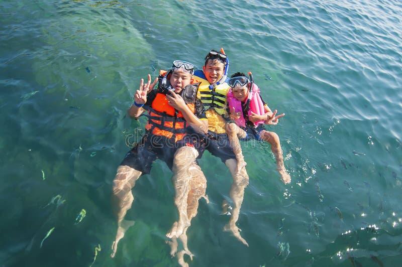 愉快地漂浮在海的三个人 免版税图库摄影
