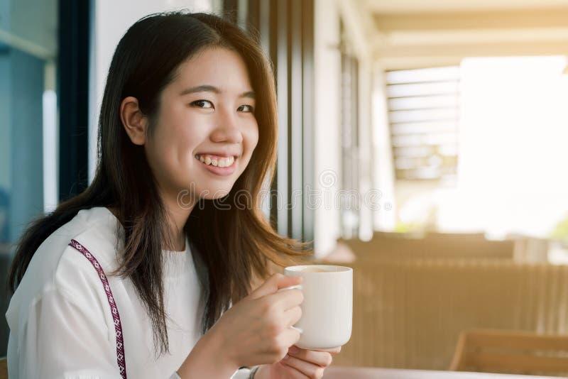 愉快地穿白色衬衫,开会,饮用的热的咖啡的亚裔美女在面包店明亮早晨 库存照片