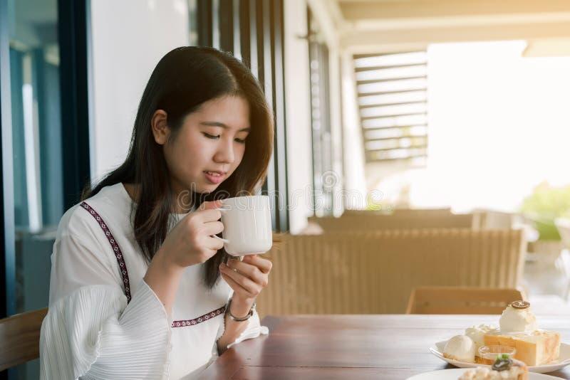 愉快地穿白色衬衫,开会,饮用的热的咖啡的亚裔美女在面包店明亮早晨 免版税库存照片