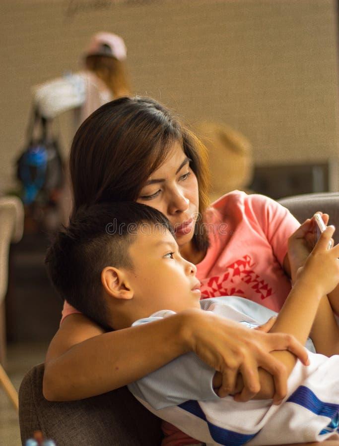 愉快地观看电话的母亲和儿子 免版税库存图片