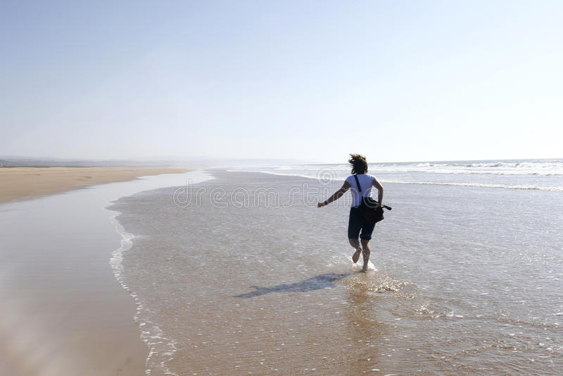 愉快地运行妇女年轻人的海滩 免版税库存图片