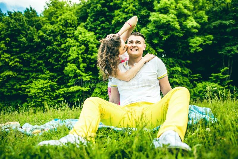 愉快夫妇放松室外在绿色公园 免版税库存照片