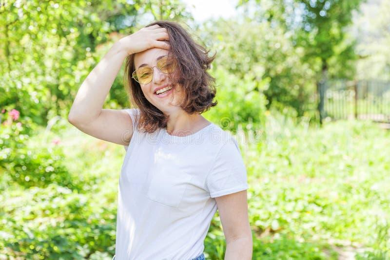 愉快女孩微笑 笑时髦黄色太阳镜的秀丽画象年轻愉快的正面深色的妇女在公园或 免版税图库摄影