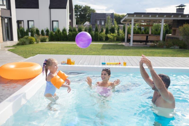 愉快女孩的感觉,当打与父母的球水池的时 免版税库存图片