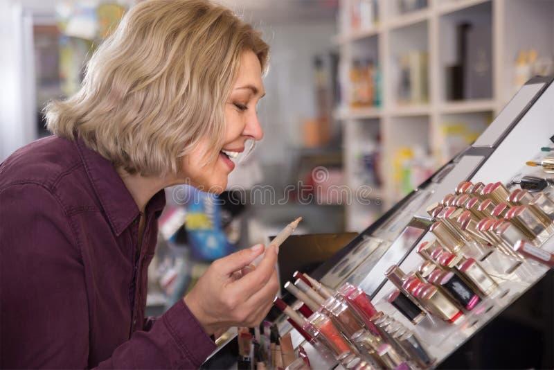 愉快女性顾客买lipstic 库存图片