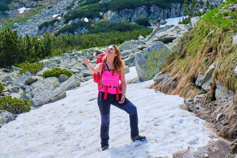 愉快妇女投掷悬而未决雪球,穿一件紫红色的衬衣,有一个重,红色背包的,在远足游览的一个夏天期间 库存照片