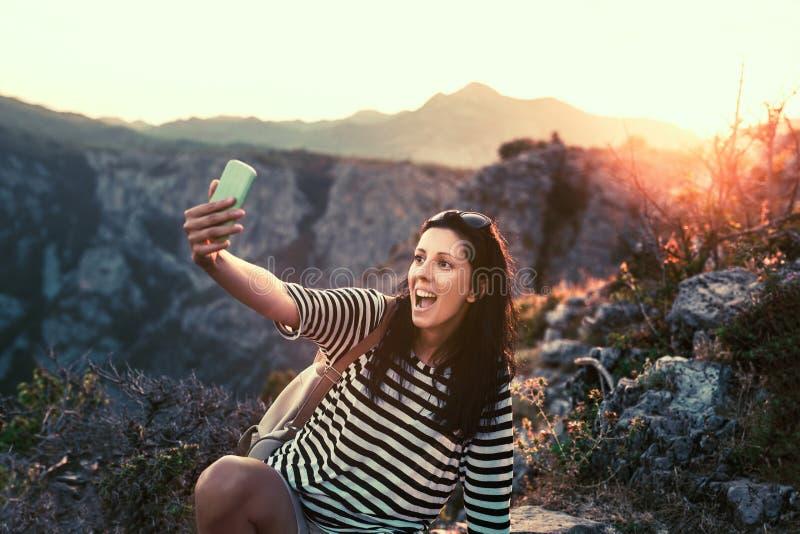 愉快妇女拍摄,采取在山峰的一selfie 库存照片