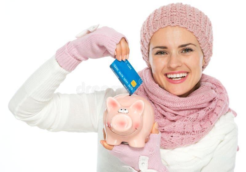 愉快妇女放置信用卡在存钱罐中 免版税库存照片